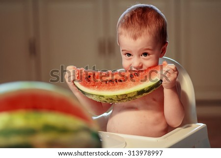 Cute topless little boy sitting in the child chair and eating big piece of watermelon. Image with toning and selective focus - stock photo