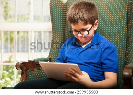 Cute tween wearing glasses and playing video games on a tablet computer at home - stock photo