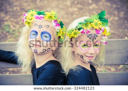 Cute twin girls smiling with sugar skull makeup on a wooden bench - stock photo