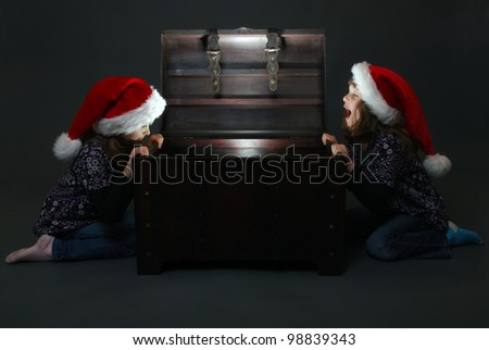 cute twin girls with santa hats found a treasure - stock photo