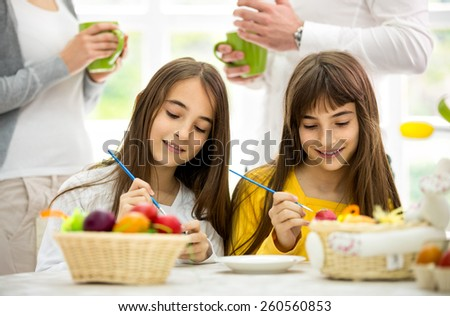 Cute twins girls decorating Easter eggs - stock photo