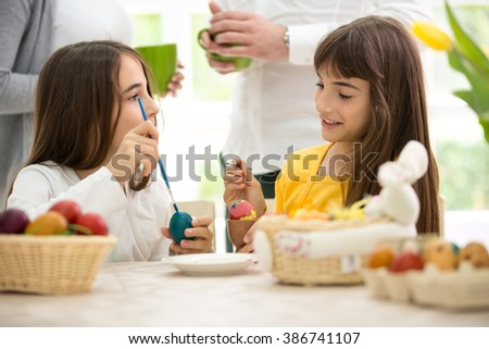 cute twins girls painted Easter eggs at home  - stock photo