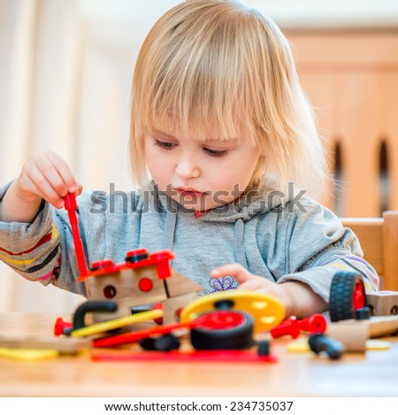 cute two-year old baby girl at home in the nursery playing with constructor - stock photo