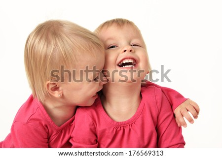 Cute two year old identical twin girls laughing - stock photo