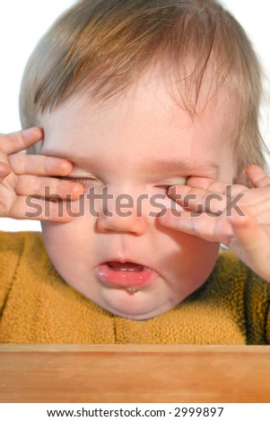 cute very tired baby rubbing eyes with his/her hands - stock photo