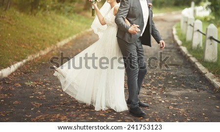 Cute wedding couple, bride and groom walking together in park.  - stock photo