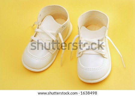 cute white child's shoes isolated over yellow - stock photo