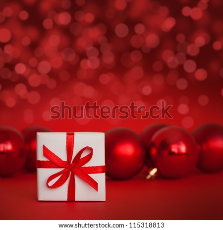 Cute white gift with red christmas balls on red abstract light background - stock photo
