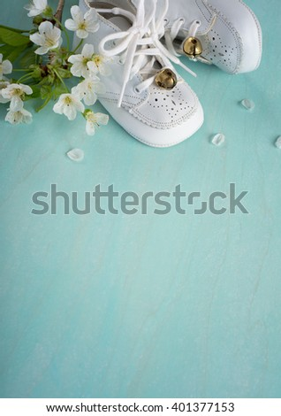 Cute, White Vintage Leather Infant Baby Shoes with spring flowers on Cyan Turquoise Faux Painted, Rustic wood Board Background with room or space for copy, text, your words. Vertical aerial side view - stock photo