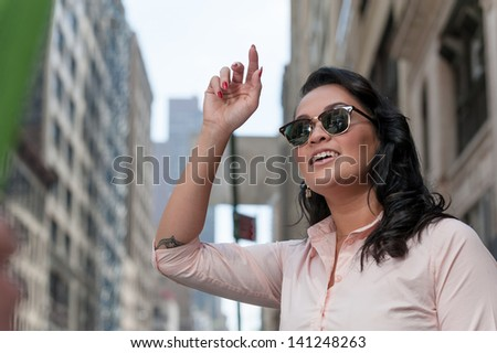 Cute woman hails taxi in NYC - stock photo