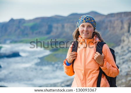 Cute woman hiking in the canyon Dettifoss waterfall in Vatnajokull National Park, Northeast Iceland. - stock photo