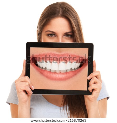 Cute woman holding a tablet with her teeth - stock photo
