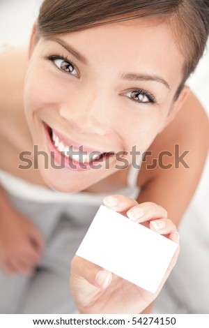 Cute woman holding business card. Beautiful mixed race Asian Chinese / Caucasian young woman in high angle view. - stock photo