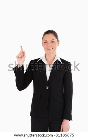 Cute woman in suit pointing at a copy space while standing against a white background - stock photo