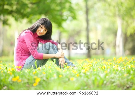 Cute woman in the park with dandelions - stock photo