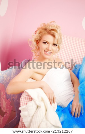 Cute woman looks like a doll in a sweet interior. Young pretty smiling girl - stock photo