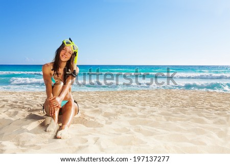 Cute woman resting after snorkling sitting on white sand and smiling wearing scuba - stock photo