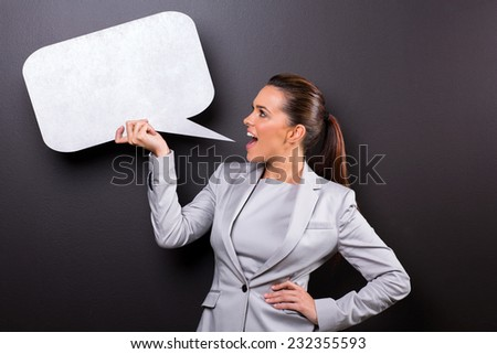 cute woman screaming in blank speech bubble isolated on black background - stock photo