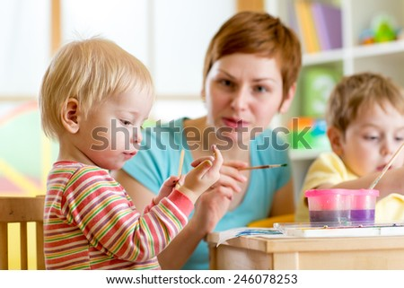 cute woman teaching children to paint at kindergarten or home or playschool - stock photo