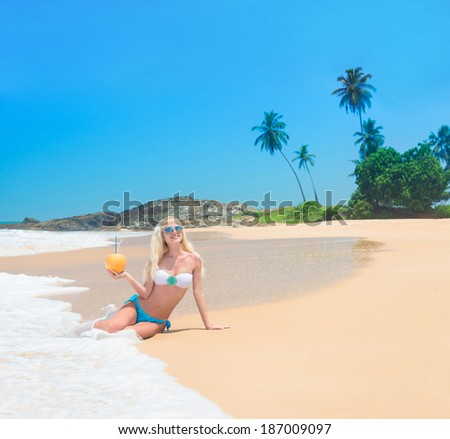 Cute woman with coconut at ocean beach against palm trees - stock photo