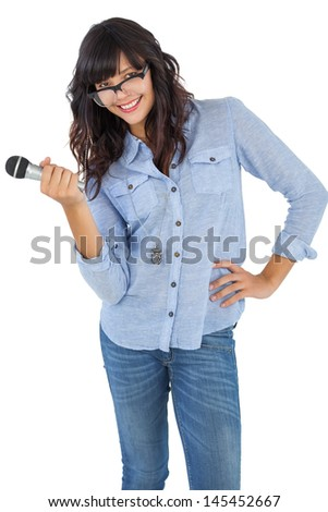 Cute woman with her hand on hip holding microphone on white background - stock photo