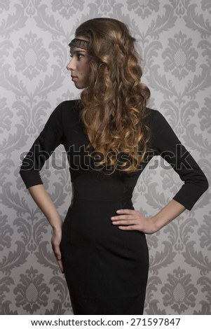 cute woman with long wavy hair posing turned in profile in fashion shoot with charming style and wearing dark elegant dress  - stock photo