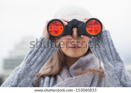 Cute woman with winter clothes on looking through binoculars outdoors on a cold grey day - stock photo