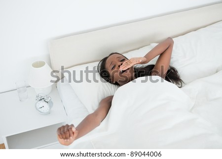 Cute woman yawning and stretching her arms while waking up in her bedroom - stock photo