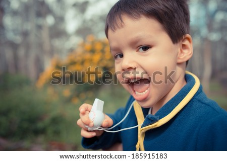 Cute 4 year old asian caucasian boy plays with a whistle outdoors in the park in Sydney, Australia - stock photo