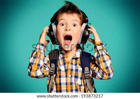 Cute 7 year old boy listening to music on headphones. - stock photo
