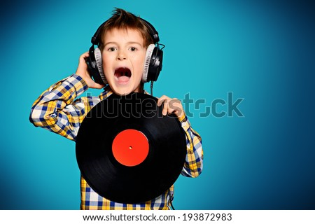 Cute 7 year old boy listening to music on headphones and holds vinyl record. - stock photo