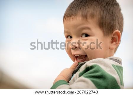Cute 2 year old mixed race Asian Caucasian boy looks cheekily at the camera.. - stock photo