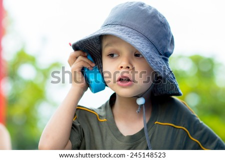Cute 4 year old mixed race Asian Caucasian boy plays outside in a playground with a toy walkie talkie radio - stock photo