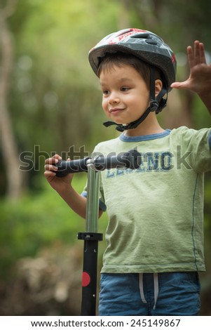 Cute 4 year old mixed race Asian Caucasian boy wearing a bike helmet cheerfully plays on his scooter on a green forest road - stock photo