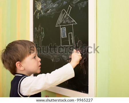 Cute 3 years old boy draws house on blackboard - stock photo