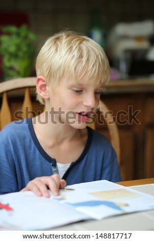 Cute 7 years old boy is studying after school, sitting on a chair in the kitchen and reading his book with home task - stock photo