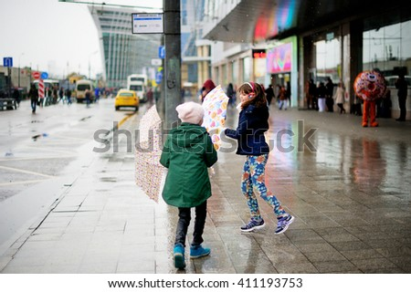 Cute 10 years old girls in light fashion jackets walking outdoors with umbrellas at rainy city - stock photo