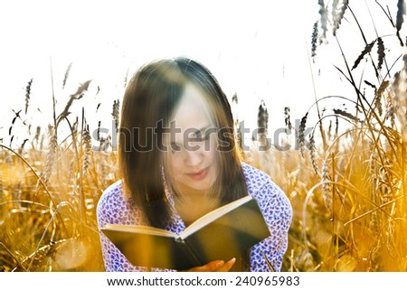 Cute young adult girl sitting on ripening ears of wheat field against  background of the setting sun set, reading  dark satan black magic book Brunette long hair woman serious look at paper page - stock photo