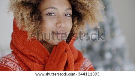 Cute young African woman in winter fashion wearing a festive red sweater and gloves posing in front of a decorated Christmas tree - stock photo