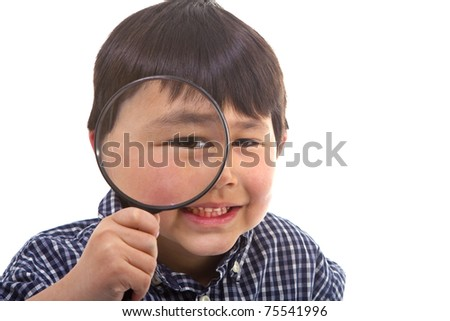 Cute young asian boy looking through a large magnifying glass isolated on white background - stock photo