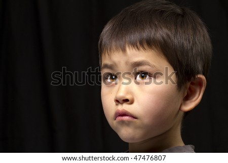 Cute young asian boy looking up on dark background - stock photo