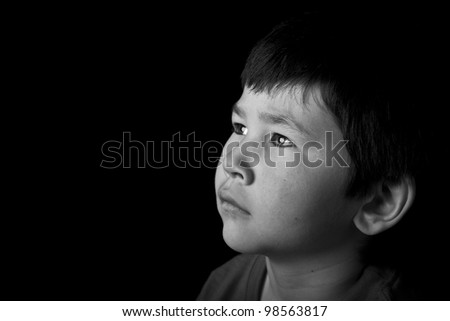 Cute young asian boy looking up with serious look on black background in black and white - stock photo