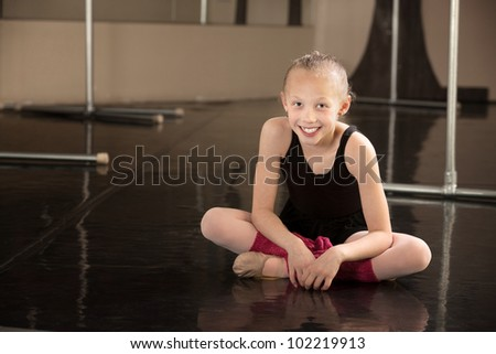 Cute young ballerina sitting on a dance floor - stock photo