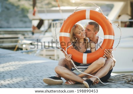 Cute young beautiful couple sitting on the ground in city near yachts with a lifebuoy and having fun together laughing and smiling kissing - stock photo