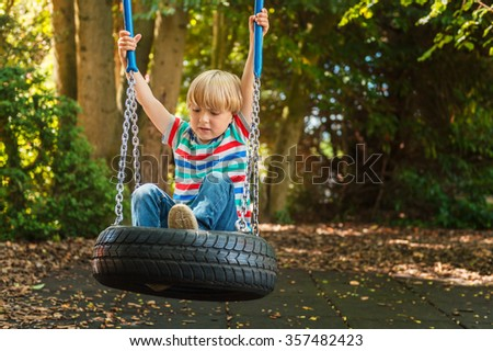 Cute young blond boy having fun on a swing on a nice summer day, wearing stripe tee - stock photo