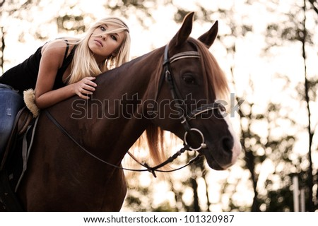 Cute young blonde riding horse - stock photo