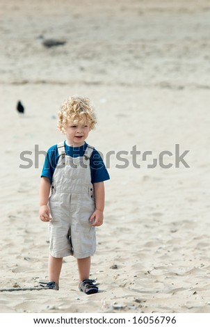 cute young boy at the beach - stock photo