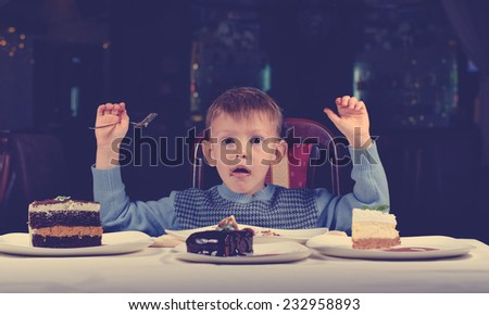 Cute young boy celebrating his birthday with a line up of different cake in front of him pulling a comic face as he tries to make up his mind where to begin eating - stock photo