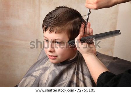 cute young boy getting a haircut - stock photo