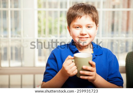 Cute young boy holding a coffee mug and smiling while relaxing at home - stock photo